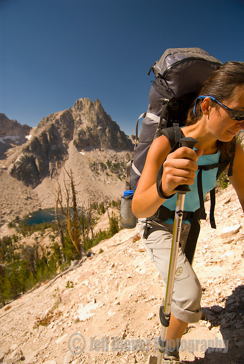 A young woman hikes up a steep hill above Warbonnet Lakes in the Sawtooth Mountains, Idaho.