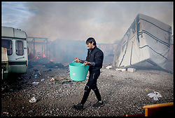 October 27, 2016 - Calais, Northern France, France - Image ¬©Licensed to i-Images Picture Agency. 27/10/2016. Calais, France. Calais Jungle Migrant Camp. A refugee carrying water to put out a fire amongst the remains of  the migrant camp as Refugees leave the Calais Jungle migrant camp the day after it caught fire and the French police closed it down. Picture by Andrew Parsons / i-Images (Credit Image: © Andrew Parsons/i-Images via ZUMA Wire)