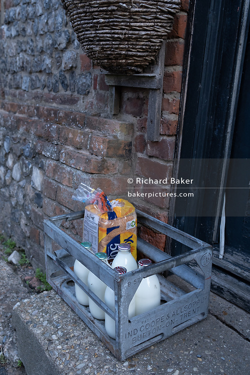 Early morning milk and bread delivery left in a crate on the doorstep of a property known as 'Geoffrey the Dyer's house', in Worstead, a village whose wealth came from the 14th century weaving industry, on 10th August 2020, in Worstead, Norfolk, England.