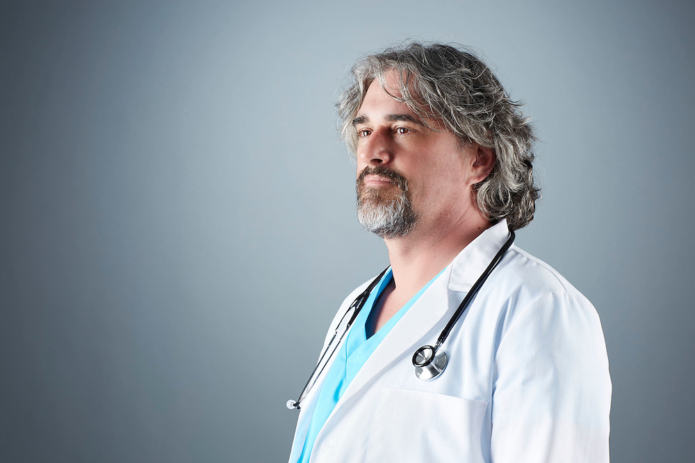 A portrait series representing the intense emotions that Doctors face.  A male Doctor wearing a white lab coat, stethoscope, and blue medical scrub suit shown.