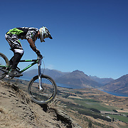 Matthew Scoles from Alexandra in action during the New Zealand South Island Downhill Cup Mountain Bike series held on The Remarkables face with a stunning backdrop of the Wakatipu Basin. 150 riders took part in the two day event. Queenstown, Otago, New Zealand. 9th January 2012. Photo Tim Clayton