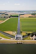 Nederland, Noord-Holland, Medemblik, 14-07-2008; gemaal De Lely, een van de twee gemalen verantwoordelijk voor het droogmalen van de Wieringermeer; in de achtergrond een enorm kassencomplex, a-typisch in jet klassieke polderlandschap; de waterhuishouding van de polder wordt mede verzorgd door de drie vaarten die naar het gemaal lopen; pomp, pompen, drainage;.pumping-station responsable for reclaiming former lake, now the biggest polder in the old land; impolder, impolderisation; the pumping-engines are used for maintaining water leves and drainage in the polder, watermanagement. .luchtfoto (toeslag); aerial photo (additional fee required); .foto Siebe Swart / photo Siebe Swart
