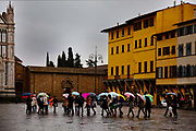 Students with umbrellas crossing St Stephens Square, Florence, in the rain.
