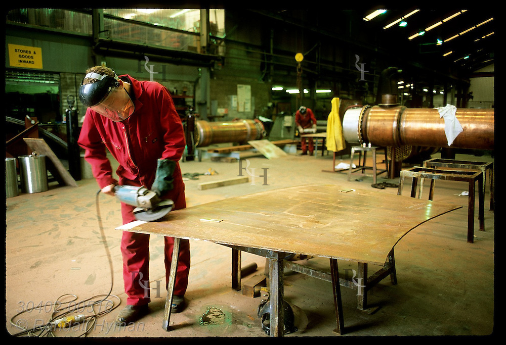 Worker grinds copper plate for assembly of pot still at Forsyth & Son metalsmiths; Rothes/Speyside Scotland