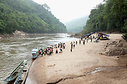 Local people from nearby villages arrive by boat to visit the small monthly market at the Khmu village of Ban Phatao, Phongsaly province, Lao PDR. The market traders travel along the Nam Ou visiting different villages selling every kind of Chinese and Vietnamese product that one might need - like biscuits and flip flops, washing powder and salt. Ban Phatao will soon be temporarily relocating away from the Nam Ou river due to the construction of the Nam Ou Cascade Hydropower Project Dam 5.