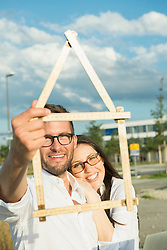 Happy couple with model house