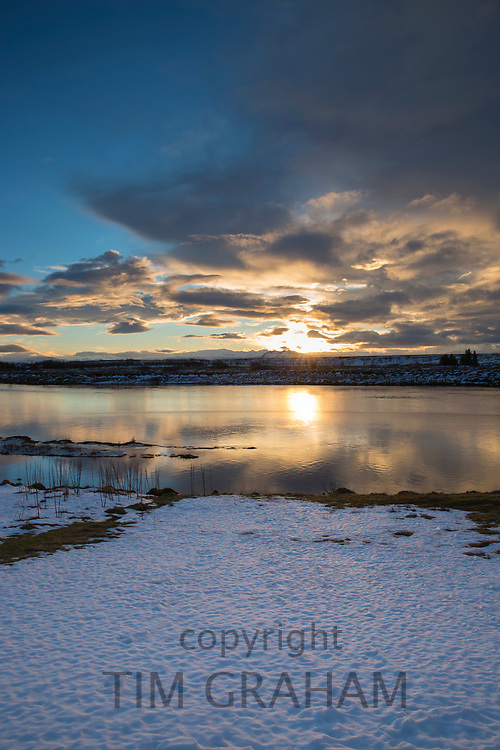 River Ranga and setting sun and puffy clouds over typical Icelandic landscape in Hella, South Iceland