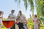 A group of visiting wine enthusiasts tasting the rose wine in the garden in summer, close up of a glass of rose rosé wine Chateau Kirwan, Cantenac Margaux Medoc Bordeaux Gironde Aquitaine France