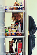 Young woman with a food craving goes through her pantry looking for a snack