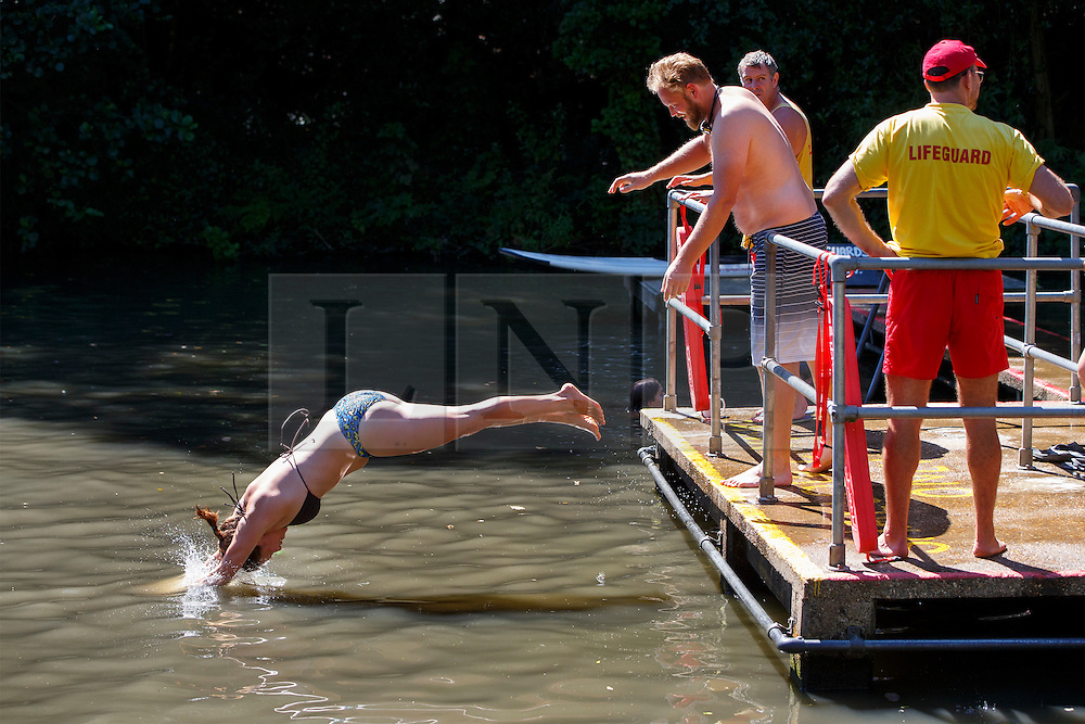 © Licensed to London News Pictures. 12/08/2016. London, UK. People swim in Hampstead Heath Mixed Bathing Pond in north London as they enjoy hot weather on Friday, 12 August 2016. Photo credit: Tolga Akmen/LNP