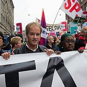 Amsterdam, 21-09-2013.  Vanuit 16 steden in het land kwamen bussen naar Amsterdam met betogers die meededen aan de demonstratie tegen de geplande bezuinigingen van het kabinet. De organisatie Comité Stop Bezuinigingen schatte de opkomst op ongeveer 5000 mensen. De manifestatie begon op het Beursplein. Vandaar trokken de demonstranten naar het beeld van de Dokwerker op het Jonas Daniël Meijerplein. Daar werd gesproken door onder andere SP-leider Emile Roemer en Henk Krol (50Plus). Meer dan 50 maatschappelijke organisaties hebben hun steun toegezegd aan de protestactie. Onder meer de Amsterdamse afdelingen van FNV Bondgenoten, Abvakabo FNV en SP en GroenLinks namen het initiatief tot de demonstratie. Zij menen dat de bevolking ,,het niet langer pikt'' dat de regering weer miljarden wil bezuinigen op onder meer zorg en kinderopvang. Volgens het comité worden de kosten van de crisis afgewenteld op kwetsbare groepen in de samenleving en worden ,,bonussen, belastingontwijking en de topinkomens nauwelijks aangepakt''. Op de foto Henricus (Harry) van Bommel, een Nederlands politicus. Namens de SP is hij sinds 1998 lid van de Tweede Kamer der Staten-Generaal.