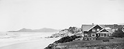 9107-10. Cottages dot the terrace overlooking Nye Beach. In the foreground is the A. L. Thomas residence, built in 1910-1911. In 1912, the Nicolai Hotel was built in the area behind it. The camera position is on the south cliff overlooking what is now the Nye Beach loop, and pointed north. The area in the foreground is now the site of the Nye Beach Hotel. Yaquina Head lighthouse in the background.