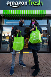 "© Licensed to London News Pictures. 07/03/2021. LONDON, UK.  Shoppers Tolu (L) and Kayanna show off their purchases outside the new 2,500 sq ft Amazon Fresh store in Ealing, west London on its first weekend of opening. It is the first ""just walk out"" grocery store in the UK and the first outside the USA.  As a ""contactless"" shop, it is available to anyone signed up to Amazon and with the app on their smartphone.  In-store cameras and artificial intelligence monitor customers picking up items who simply walk out and billing takes place later automatically.  Photo credit: Stephen Chung/LNP"