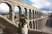 Tourist taking selfie photographs with smartphone on selfiestick at famous spectacular Roman aqueduct, Segovia, Spain
