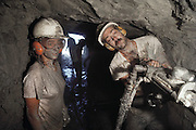 Corey Wilson and John Wilson, members of the Dinosaur Cove excavation team, drill holes in the working face of the mine to allow explosives to be placed. The explosives are used to dislodge large pieces of rock, which are then removed and checked for fossil remains. Dinosaur Cove is the world's first mine developed specifically for paleontology, normally the scientists rely on commercial mining to make the excavations. The site is of particular interest as the fossils found date from about 100 million years ago, when Australia was much closer to the South Pole than today. MODEL RELEASED [1989].