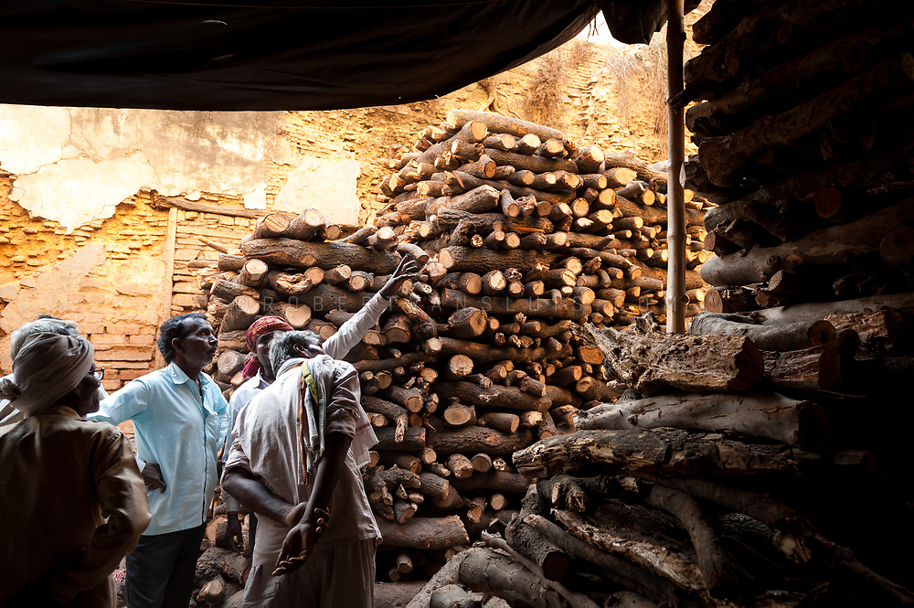 A family selects wood for a cremation at Manikarnika cremation ground. Photo © robertvansluis.com