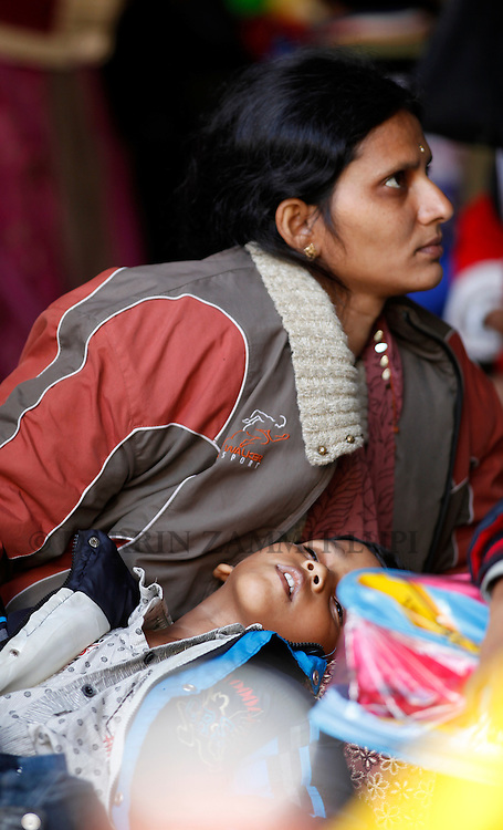 An Indian child sleeps on his mother's lap while waiting to disembark from the ferry MV Red Star One after arriving at Valletta's Grand Harbour March 6, 2011.  The Indian-chartered ferry arrived in Malta from Misurata in Libya on Sunday morning carrying 301 evacuees, mostly Indians but also including Filipino, British and Bangladeshi nationals...REUTERS/Darrin Zammit Lupi (MALTA)