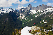 Ian Derrington stands on the summit ridge of Damnation Peak looking out towards Mount Triumph, North Cascades National Park, Washington.