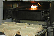 Israel, Haifa, Wadi Nisnas, Baking pita in an oven