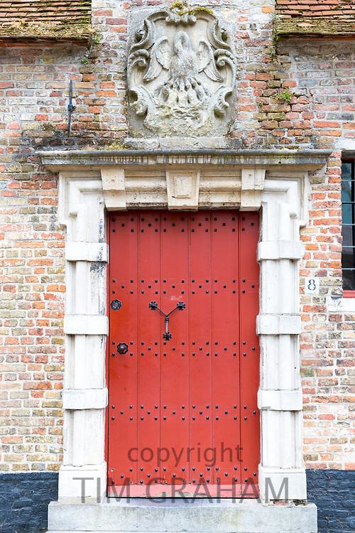 Traditional door and doorway painted bright red in old town Bruges - Brugge - Belgium