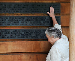 CENTRAL LONDON. A woman points touches a name on the memorial wall. Family and friends of those killed in the World Trade Centre attacks in New York in 2001 visit the memorial to the British victims in Grosvenor Square.  11 September 2010. STEPHEN SIMPSON.