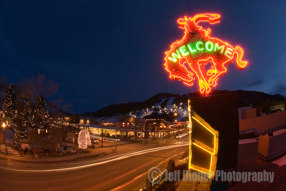 The Million Dollar Cowboy Bar neon bronco and the Jackson Town Square glow at night in Jackson, Wyoming.