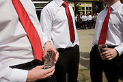Holding empty pint glasses that symbolises an empty economic recession, City of London office workers gather to drink at lunchtime while dressed in red ties and white shirts, on the 23rd April, St George's Day, England's national day.