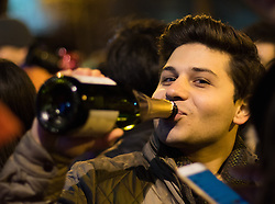 London January 1st 2016. As London waits to welcome the new year  with a spectacular fireworks display on the banks of the River Thames, one of the tens of thousands of spectators enjoys a swig of bubbly.