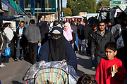 Woman wearing a burkha and people from various ethnic backgrounds around the market on Whitechapel High Street in East London. This area in the Tower Hamlets is predominantly Muslim with just over 50% from Bangladeshi descent. This is known as a very poor area of London's East End.