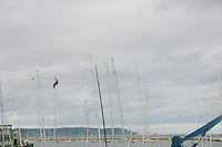 Man on top of boat sail, Dun Laoghaire Harbour, Dublin, Ireland<br />