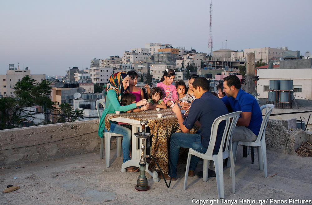 Youth play cards on a roof top in the Dheisheh refugee camp. The camp is overbuilt and the roof provides a breeze and space to breath.