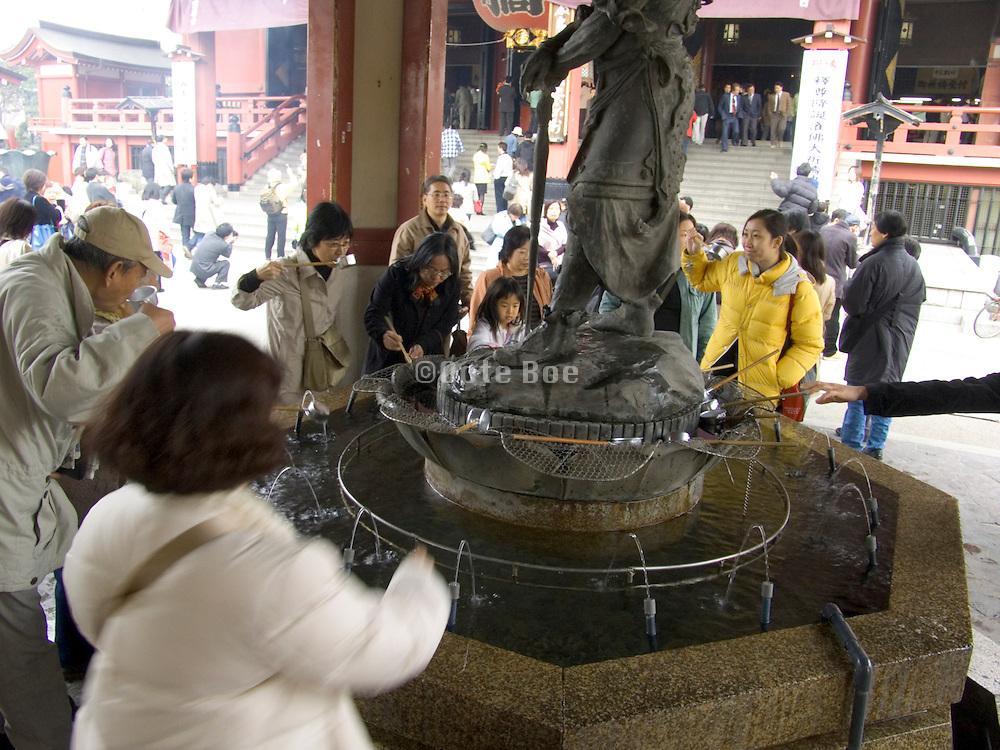 people drinking water at the Asakusa Kannon Temple Tokyo
