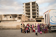 Syrian women and children wait to be seen by medical staff at a mobile clinic outside a former wedding hall which now hosts hundreds of Syrians displaced from Kobane/Ayn al-Arab during fighting between Kurdish groups and ISIS.