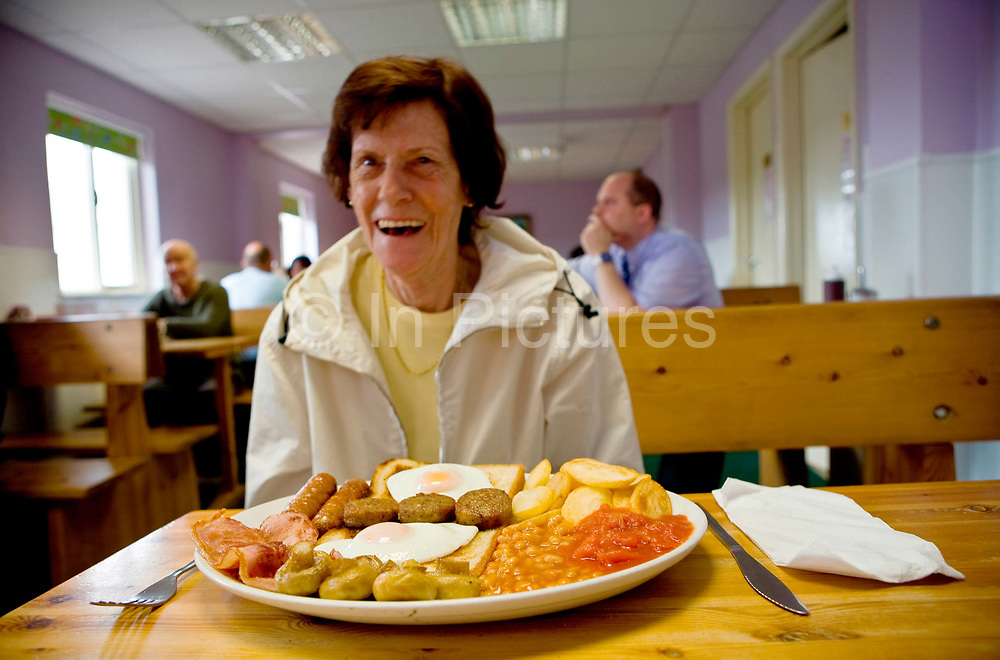 Pat, a retired waitress sitting at a table with a huge full English breakfast at Smokey Joe's transport cafe on 05th June 2008 in Blackwater in the United Kingdom. Smokey Joe's is a renowned cafe off the A30 in Blackwater in Cornwall.