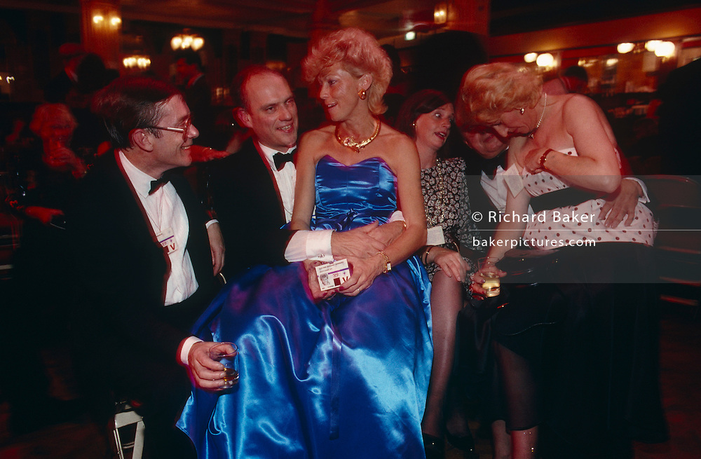 Six delegates sit down in good humour at the annual Party Conference of 1993 at Blackpool during the premiership of Prime Minister Margaret Thatcher. In the centre of frame a lady is sitting on her partner's lap, holding her security pass and wearing a chintzy royal blue ball gown. The male friend is holding her around the waist with both hands and they chat with a third person on the end. Behind the lady in blue are three other people, one of whom is inspecting her cleavage to the surprise of another lady who is staring wide-eyed down at the lady's bosoms. It is a humorous, ridiculous scene at a formal political function