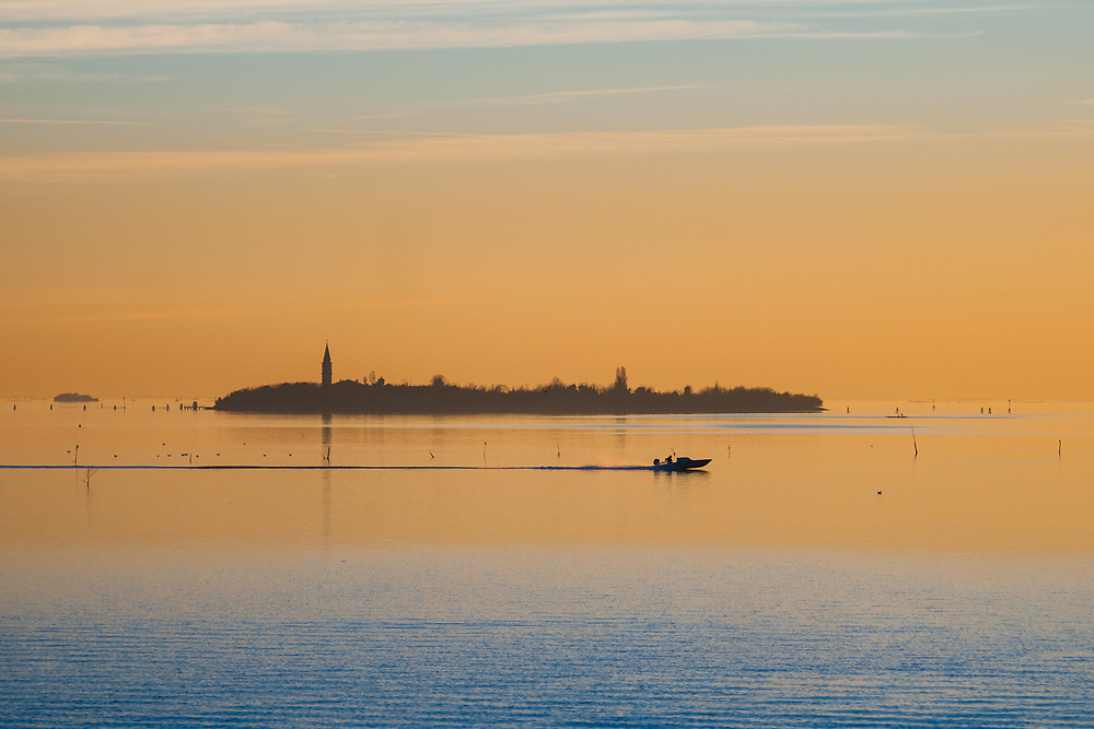 A motorboat sails the southern Venetian Lagoon at sunset.