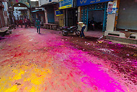 Streets covered in colored powders after procession has passed, Chhadi Mar Holi (local Holi celebration), Holi Festival (Festival of Colors), village of Gokul, near Mathura, Uttar Pradesh, India.