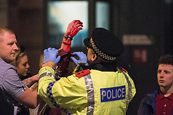 © Licensed to London News Pictures . 21/12/2013 . Manchester , UK . A police Inspector tends to a man with a bleeding arm following a fight on the city's Charlotte Street . Christmas revellers out in the rain in Manchester on Mad Friday , the last Friday night before Christmas which is typically one of the busiest nights of the year for police and ambulance crews . Photo credit : Joel Goodman/LNP