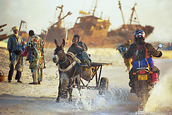 A boy using a donkey to transport fish to the local markets is splashed by a motorbike on the coast of Mauritania where local fishermen struggle to compete with the huge tankers and trawlers used by the foreign fleets. West Africa has suffered massive overfishing by foreign fishing fleets, with local small fishing boats forced to fish further and further out to sea or to concentrate their activities in sensitive coastal areas.  In the last 45 years, foreign vessels,   caught an estimated 80 percent of the fish taken from West African waters. The coastal nations took home the remaining 20 percent. And their share may get smaller. (Photo by Ami Vitale)