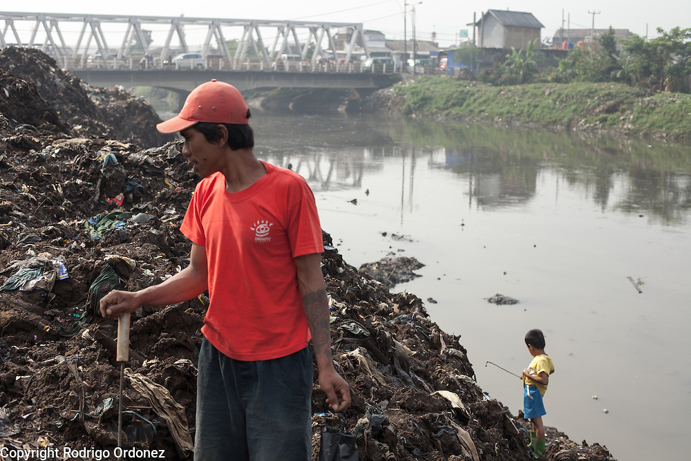 A man and his son pick through trash and collect scrap metal by the Citarum river in Kampung Bolero, Dayeuhkolot district, Bandung regency, Indonesia. Sludge and trash dredged from the riverbed is now piled up on the riverbank. ..The Citarum river, which runs about 270 kilometers through the province of West Java, is considered to be among the world's dirtiest. Over the last twenty years, the river has been severely polluted by toxic industrial waste, trash and raw sewage. The Citarum is one of the main sources of freshwater for West Java and supplies about 80% of water for Indonesia's capital Jakarta.