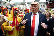 Donald Trump lookalike with chlorinated chicken dancers in Trafalgar Square during protests against the state visit of US President Donald Trump on 4th June 2019 in London, United Kingdom. Organisers Together Against Trump which is a collaboration between the Stop Trump Coalition and Stand Up To Trump, have organised a carnival of resistance, a national demonstration to protest against President Trump's policies and politics during his official UK visit.