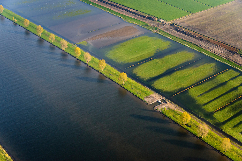 Nederland, Brabant, Gemeente Waspik, 28-10-2013; Overdiepsche polder: in het kader van het programma 'Ruimte voor de Rivier' (bescherming tegen hoogwater door rivierverruiming), is de zomerdijk langs de Bergsche Maas (met bomen) van instroomgaten voorzien, terwijl de winterdijk verlaagd wordt. De uiterwaarden zijn overstroomd, bij hoogwater kan de Overdiepse polder ook overstromen. De boerderijen in de polder zijn daarom gesloopt en verplaatst naar de dijk van het Oude Maasje. De nieuwe boerderijen met bijgebouwen staan op terpen.<br /> Depoldering of Overdiep Polder, farms are relocated and built on mounds. This makes it possible for the river to overflow the polder in case of heigh waters. The dikes have been excavated.<br /> luchtfoto (toeslag op standard tarieven);<br /> aerial photo (additional fee required);<br /> copyright foto/photo Siebe Swart