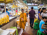 17 MAY 2013 - BANGKOK, THAILAND:   A Buddhist novice monk walks through the flower market in Bangkok on his morning alms rounds. The Bangkok Flower Market (Pak Klong Talad) is the biggest wholesale and retail fresh flower market in Bangkok. It is also one of the largest fresh fruit and produce markets in the city. The market is located in the old part of the city, south of Wat Po (Temple of the Reclining Buddha) and the Grand Palace.   PHOTO BY JACK KURTZ