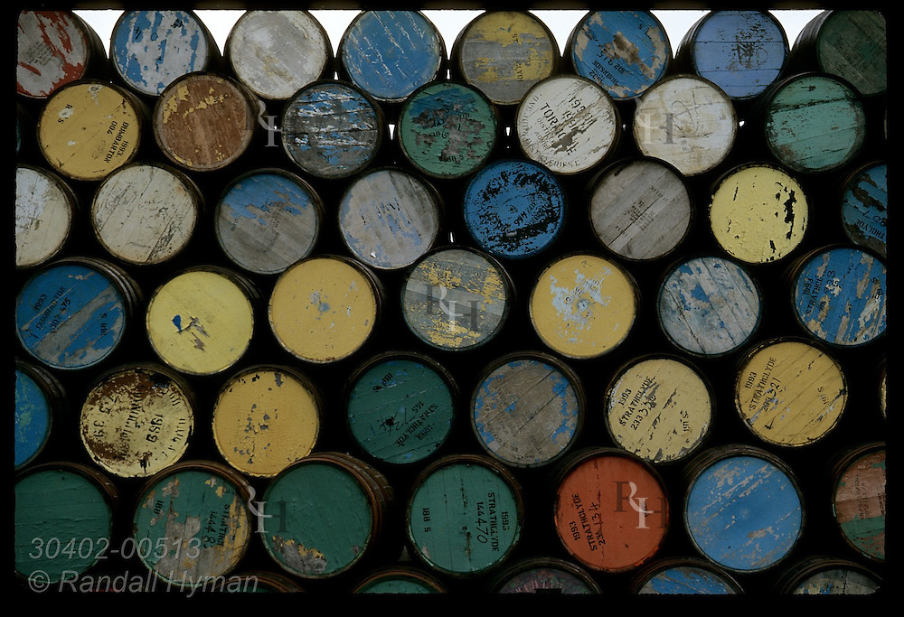 Colorful casks sit stacked in storage yard awaiting repair for use in whisky industry; Dufftown Scotland