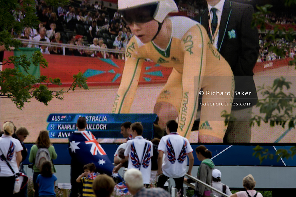 A lone Australian spectator with the national flag on the person's back in the Olympic Park, near the Velodrome, watches a heat of the  women's team sprint between Team GB and Australia - featuring the British darling of cycling Victoria Pendleton, who was later disqualified after a technical error, during the London 2012 Olympics. This land was transformed to become a 2.5 Sq Km sporting complex, once industrial businesses and now the venue of eight venues including the main arena, Aquatics Centre and Velodrome plus the athletes' Olympic Village. After the Olympics, the park is to be known as Queen Elizabeth Olympic Park.
