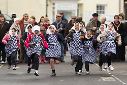 Girls from Olney middle school take part in the Olney Pancake Race which was held today, Shrove Tuesday 2013. It is the world's original pancake race dating back to 1445 and is only open to women who have lived in the town for at more than three months.   Tuesday 12  February  2013.  Olney, UK, Photo by Mark Chappell / i-Images.