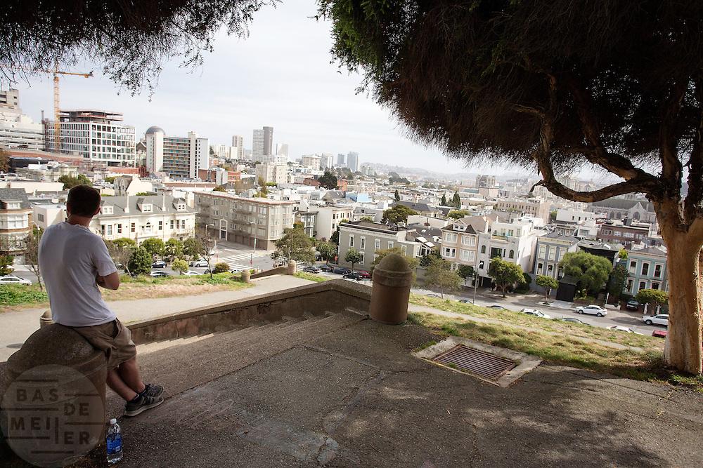 Een man kijkt vanaf het Alta Plaza Park naar San Francisco. De Amerikaanse stad San Francisco aan de westkust is een van de grootste steden in Amerika en kenmerkt zich door de steile heuvels in de stad.<br /> <br /> A man watches from the Alta Plaza Park in San Francisco. The US city of San Francisco on the west coast is one of the largest cities in America and is characterized by the steep hills in the city.