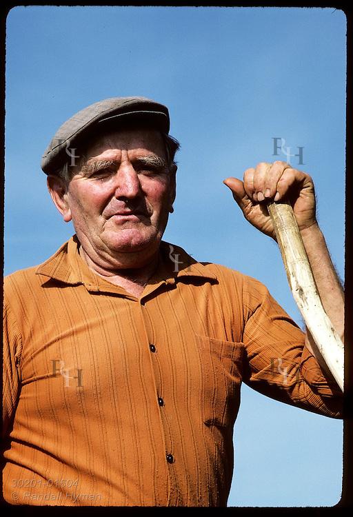 Brittany farmer leans on his scythe while posing for photo; near Brest. France