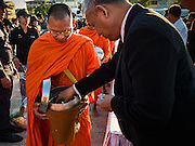 "20 JANUARY 2017 - BANGKOK, THAILAND: A man gives alms to a Buddhist monk during the ""tak bat"" (alms giving ceremony) on the plaza in front of Bangkok's City Hall. Hundreds of municipal workers and civil servants made merit by praying and presenting alms to 89 Buddhist monks Friday to mark 100 days of mourning since the death of revered Bhumibol Adulyadej, the Late King of Thailand. The significance of 89 monks is that the King, who died on October 13, 2016, was a few weeks short of his 89th birthday.       PHOTO BY JACK KURTZ"
