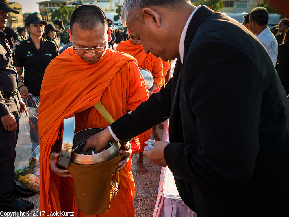 """20 JANUARY 2017 - BANGKOK, THAILAND: A man gives alms to a Buddhist monk during the """"tak bat"""" (alms giving ceremony) on the plaza in front of Bangkok's City Hall. Hundreds of municipal workers and civil servants made merit by praying and presenting alms to 89 Buddhist monks Friday to mark 100 days of mourning since the death of revered Bhumibol Adulyadej, the Late King of Thailand. The significance of 89 monks is that the King, who died on October 13, 2016, was a few weeks short of his 89th birthday.       PHOTO BY JACK KURTZ"""